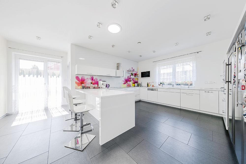 Bílá kuchyňská linka je vyhotovana ve vysokém lesku aje doplněna za pracovní deskou grafosklem skvětinovým dekorem. FOTO WIENERBERGER