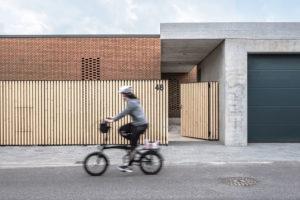 žena na kole pred domem