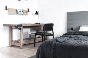 Police na časopisy ve formě dřevěných tyčí, pracovní stůl se svěrákem, noční stolek svodovodním kohoutkem.