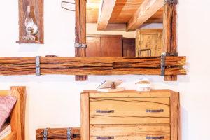 Zrcadlo apolice nad postelí byly zhotoveny ze starých trámů