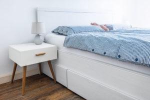 KUS SKANDINÁVIE. Ložnice je laděna vbílém severském duchu, jen sjemnými odstíny na textiliích adoplňcích. Podlaha vypadá knerozeznání od pravého dřeva, prostoru dodává hloubku azútulňuje ho. FOTO MIRO POCHYBA
