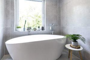 Volně stojící vana pod oknem přímo vybízí odpočívat ve voňavé lázni.