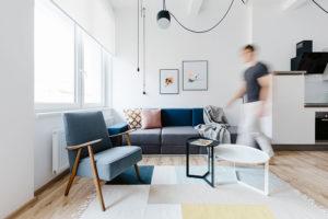 Obývací část bytu tvoří modulární pohovka, retro křesílko amalý odkládací stolek.