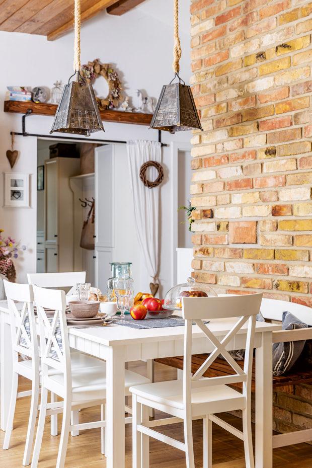 JÍDELNÍ ČÁST, která je jakýmsi centrem denní zóny, tvoří stůl ažidle doplněné rustikální lavičkou. Tu majitelé natřeli tak, aby kezbytku ladila. Iprostírání se nese ve stejném venkovském duchu jako celý interiér.