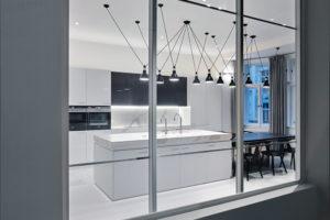 Kuchyně, která se nachází na druhém patře, je od schodiště oddělená skleněnou příčkou.