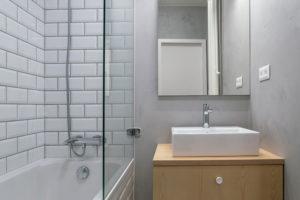 Koupelna ma geometrickým obkladem připomínajícím bílé cihly