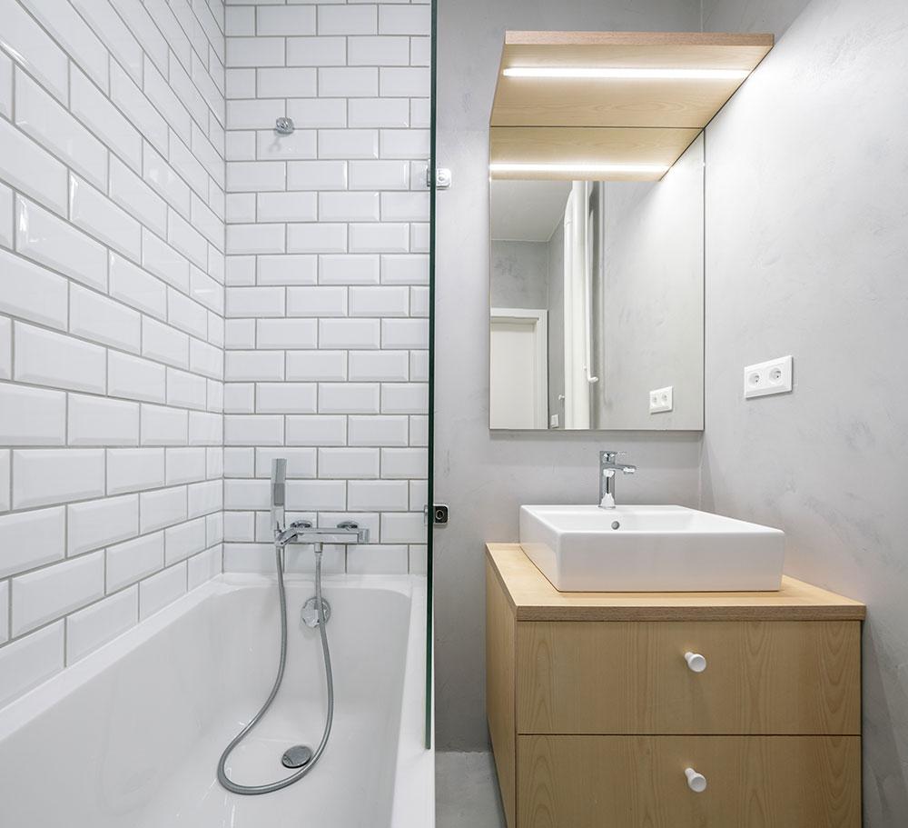 Koupelna s geometrickým obkladem připomínajícím bílé cihly