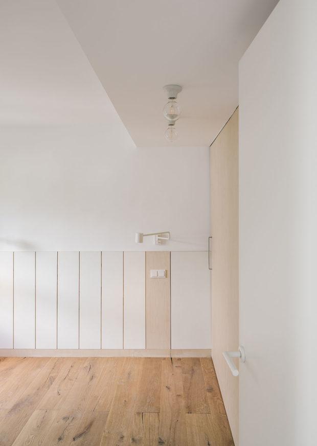 Hlavní ložnice má dřevěnou podlahu a bílou vestavěnou skříň.