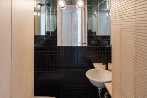 černými obkladačkami obložená toaleta s umyvadlem