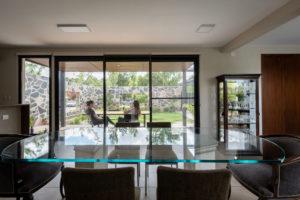 Jednopodlažní dům s obývacím pokojem mezi stromy