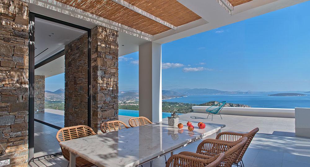 Venkovní jídelna po straně objektu, poblíž bazénu (posuvné prosklené dveře Schüco ASS 50 se při otevření zasunou do stěny z přírodního kamene). Foto: Schüco , Konstantinos Thomopoulos