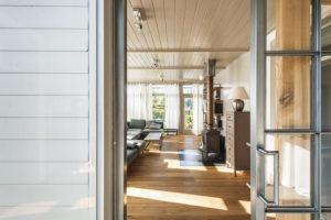 Pohled do obývacího pokoje napovídá, že je místem, kde se schází rodina. Kpocitu tepla (domova) přispívají ilitinová kamna