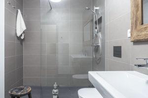 Koupelna je obložená šedým obkladem