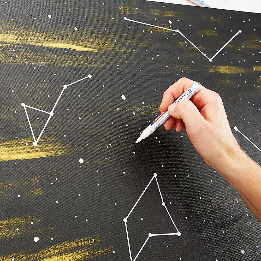 KRESLENÍ. Bílou fixkou nakreslete na obraz hvězdy apravítkem je vzájemně spojte rovnými čarami. Použít můžete ipředem připravené šablony. FOTO Möbelix