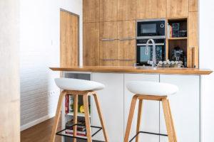 kuchyni tvoří ostrov sdostatkem pracovních ploch adíl svysokými skříněmi