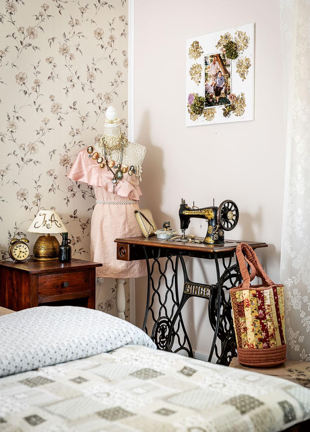 Na stěně za postelí je tapeta skvětinovým motivem, který se opakuje ina staré skříni naproti posteli či na úložných krabicích vedle. Postel inoční stolky ztmavého dřeva se pěkně doplňují se světlou podlahou astěnami. Foto Miro Pochyba