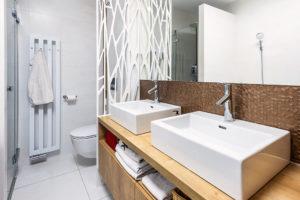 Kovová zástěna decentně odděluje WC od zbytku koupelny