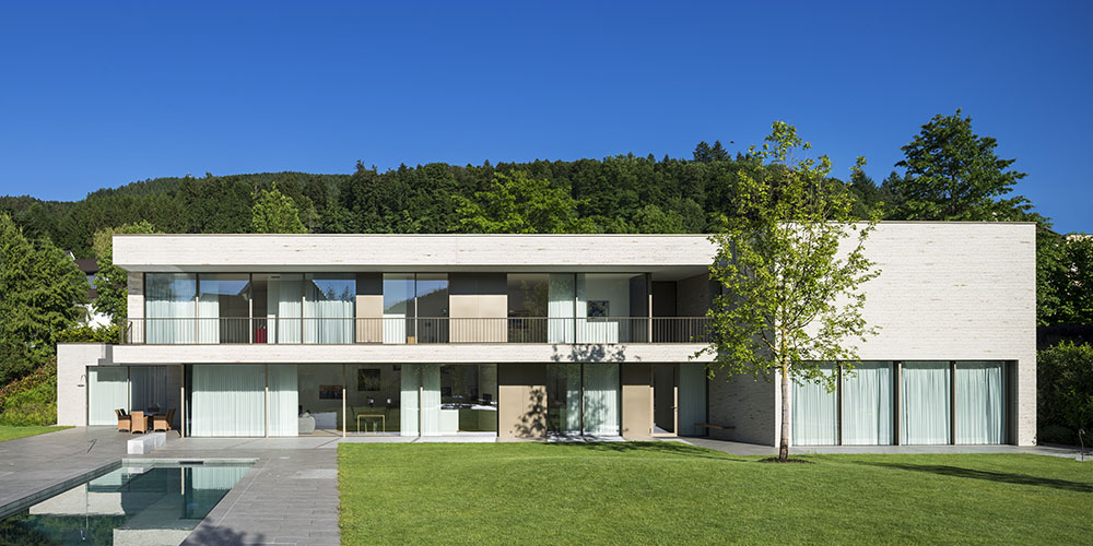 Zadní fasáda podlouhlé stavby se v obou výškových úrovních otevírá směrem do zahrady díky posuvným systémům (Schüco ASS 77 PD.SI). Foto: Harter + Kanzler & Partner, Freiburg