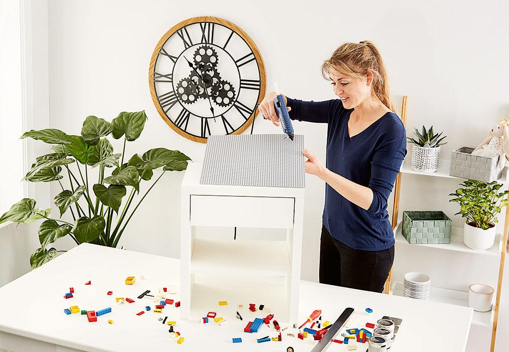 LEPENÍ DESKY. Stavebnicovou desku srozměrem asi 25 × 25cm přilepte pomocí lepicí pistole na vrchní část stolku. Foto Möbelix