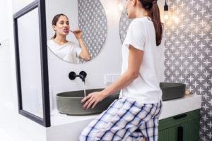 Koupelna a žena čistící si zuby
