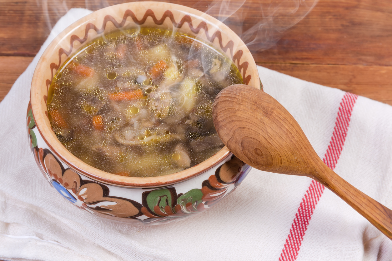 Buckwheat mushrooms soup in bowl with wooden spoon close-up