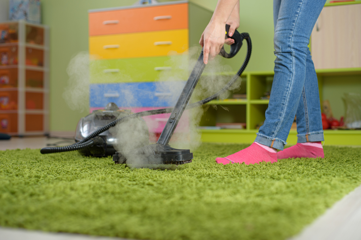 Woman cleaning carpet in the children room. getting rid of dust mites