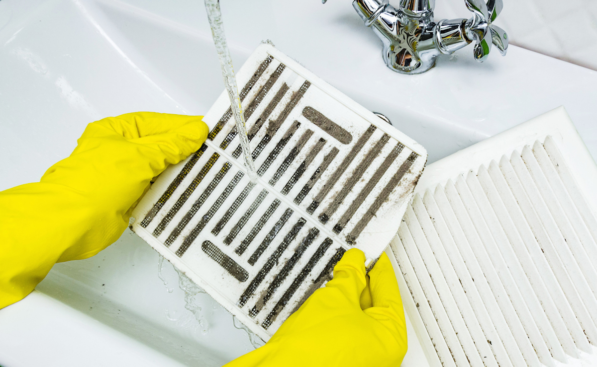 Person in a protective yellow rubber glove washes in the sink air filter of the ventilation return duct blocked by dust and debris. Cleaning service concept.