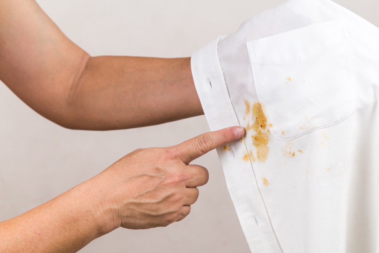 Person pointing to spilled curry stain on white shirt.