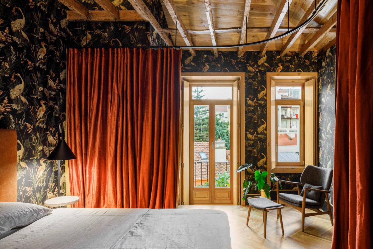 Barevná ložnice s trámy a závěsem