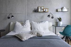 Ložnice s betonovou stěnou