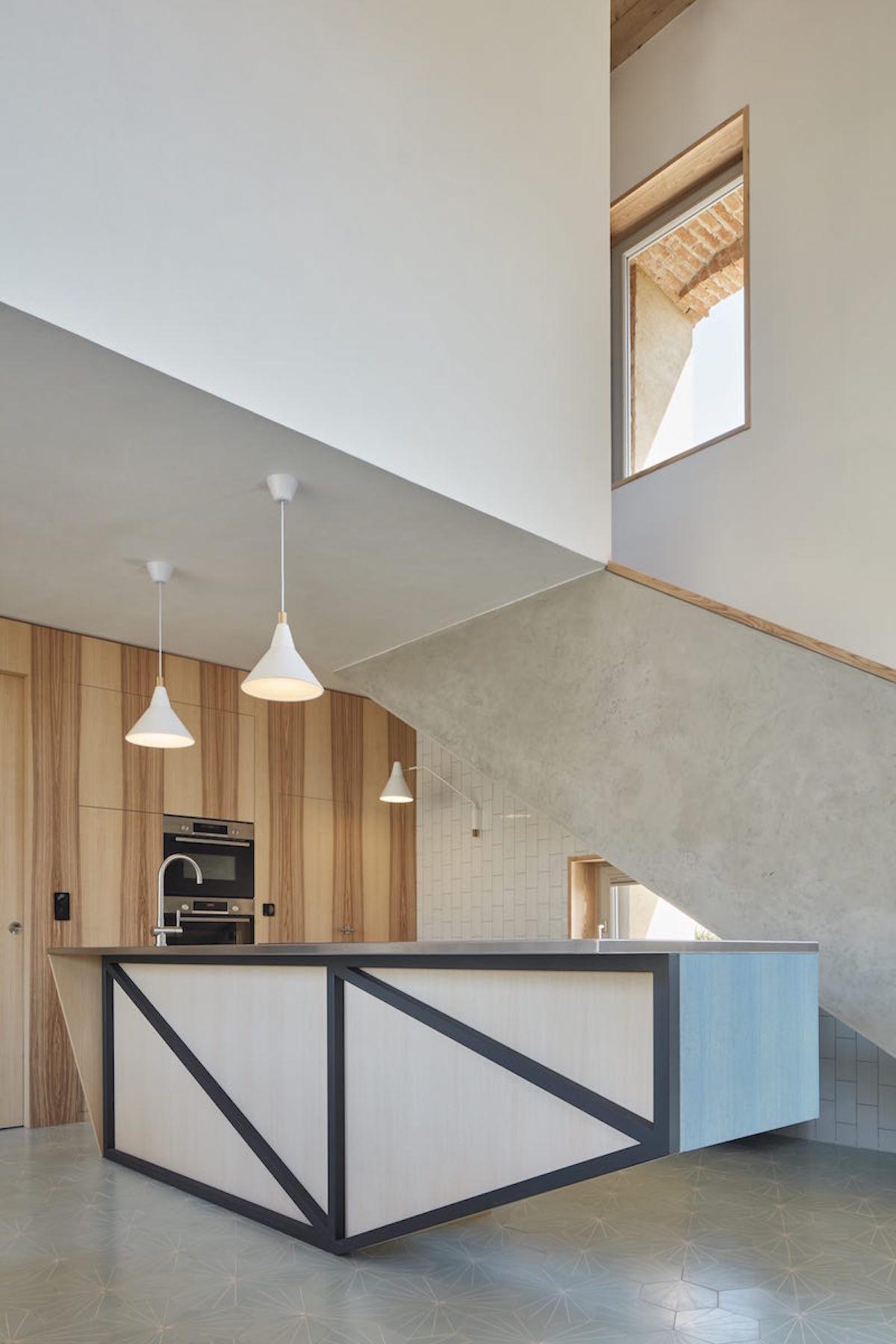 Výrazné geometrické členění a uklidňující modř kuchyňského ostrůvku