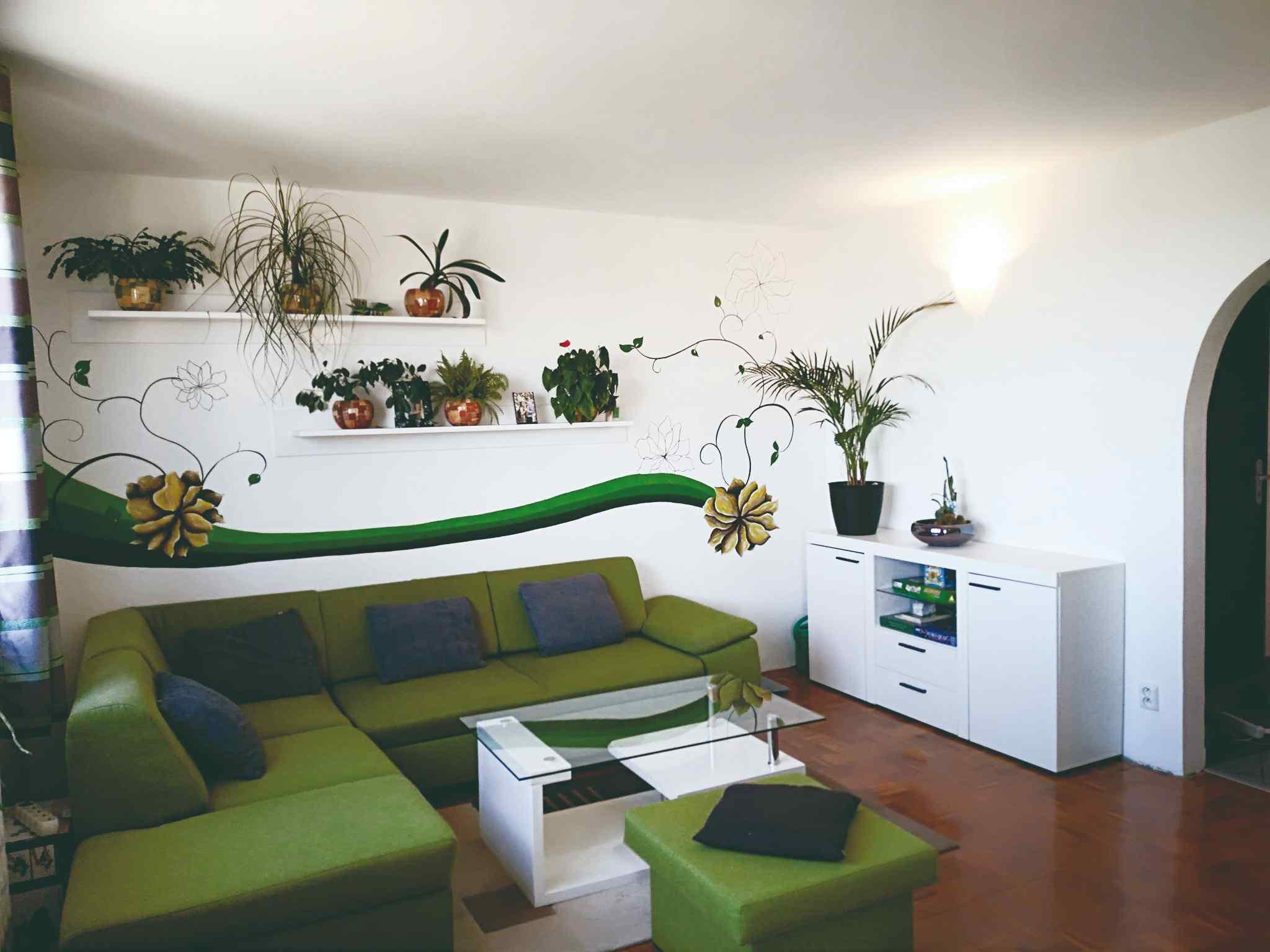 Obývák, květinové nálepky a zelená pohovka