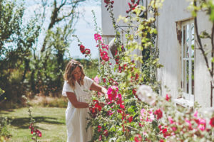 Majitelka domečku v zahradě zbírá květiny