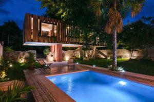 Část domu na betonové desce bazén v noci