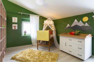 Dětský pokoj se zelenou stěnou a postýlkou