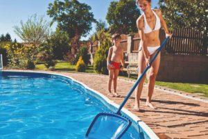 Žena používá síťku na čištění bazénu