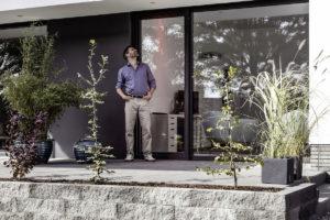 Muž stojí na terase před velkými oknami