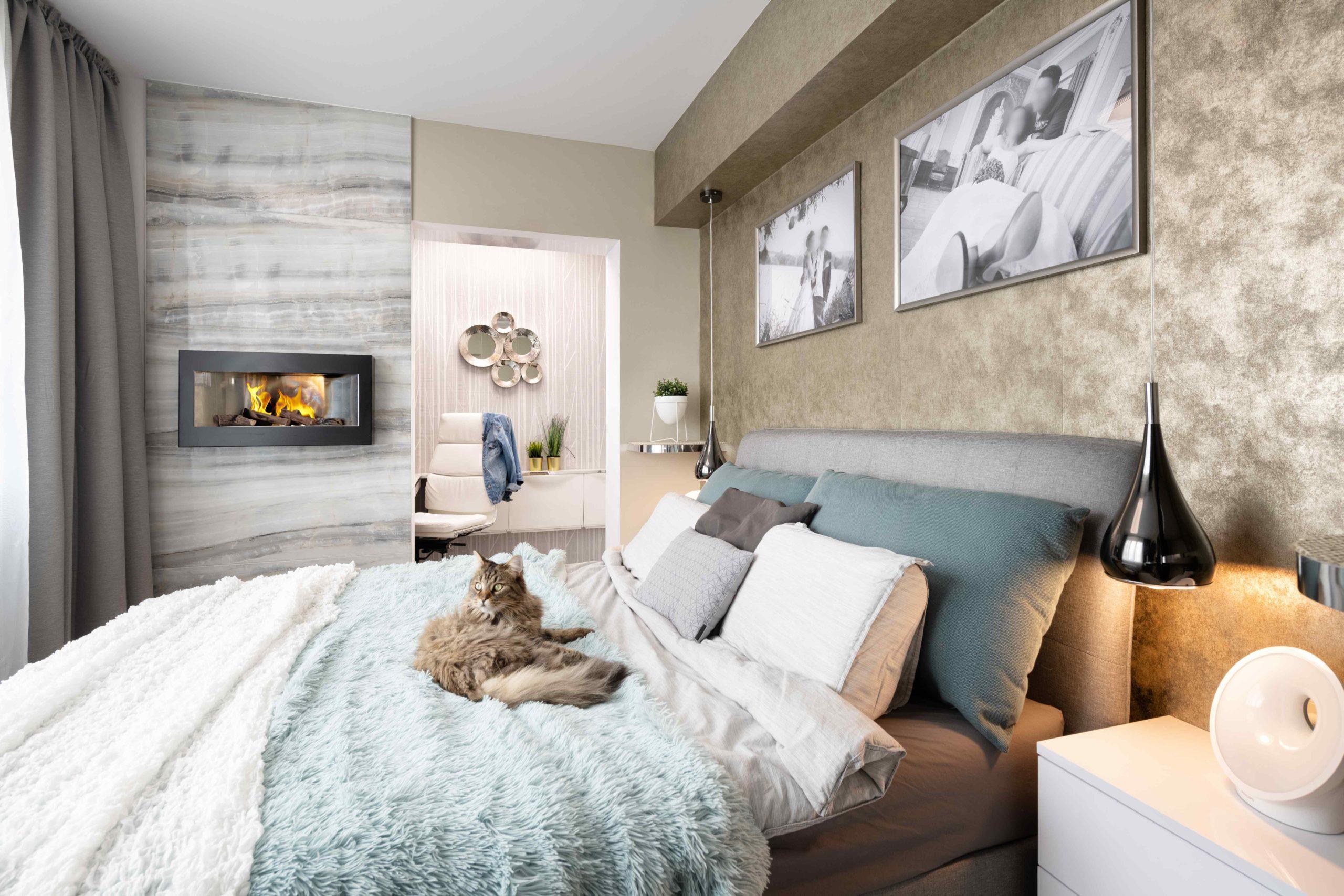 Utulná ložnice s krbem a kocourem na posteli