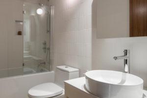 Koupelna v bílé s terazzo podlahou