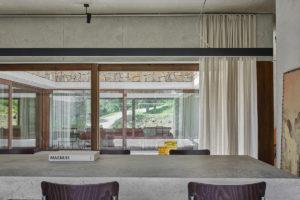 Monumentální zapuštěný cementový stůl a pohled skrz atrium