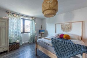 Ložnice s velkou modrou dekou a ratanovým svítidlem