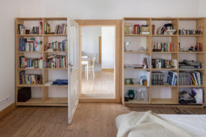 Knihovna na míru v ložnici kolem dveří