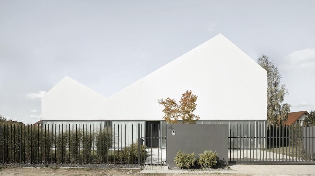 Neobvyklý rodinný dům s charakteristickou střechou a půvabným atriem