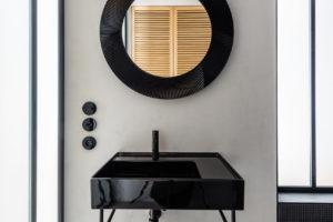 Světle šedá stěna, černé umyvadlo a zrcadlo