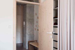 Drevěné dveře do ložnice s ratanovým lustrem