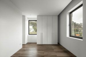 Ložnice s bílou skříní a okny