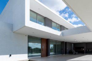 Bílý dvoupodlažní dům s prosklenou fasádou