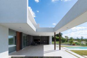 Bílý dvoupodlažní dům s otevřenou stěnou