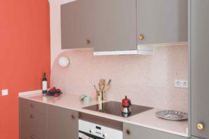 Šedá kuchyň s koralovou stěnou