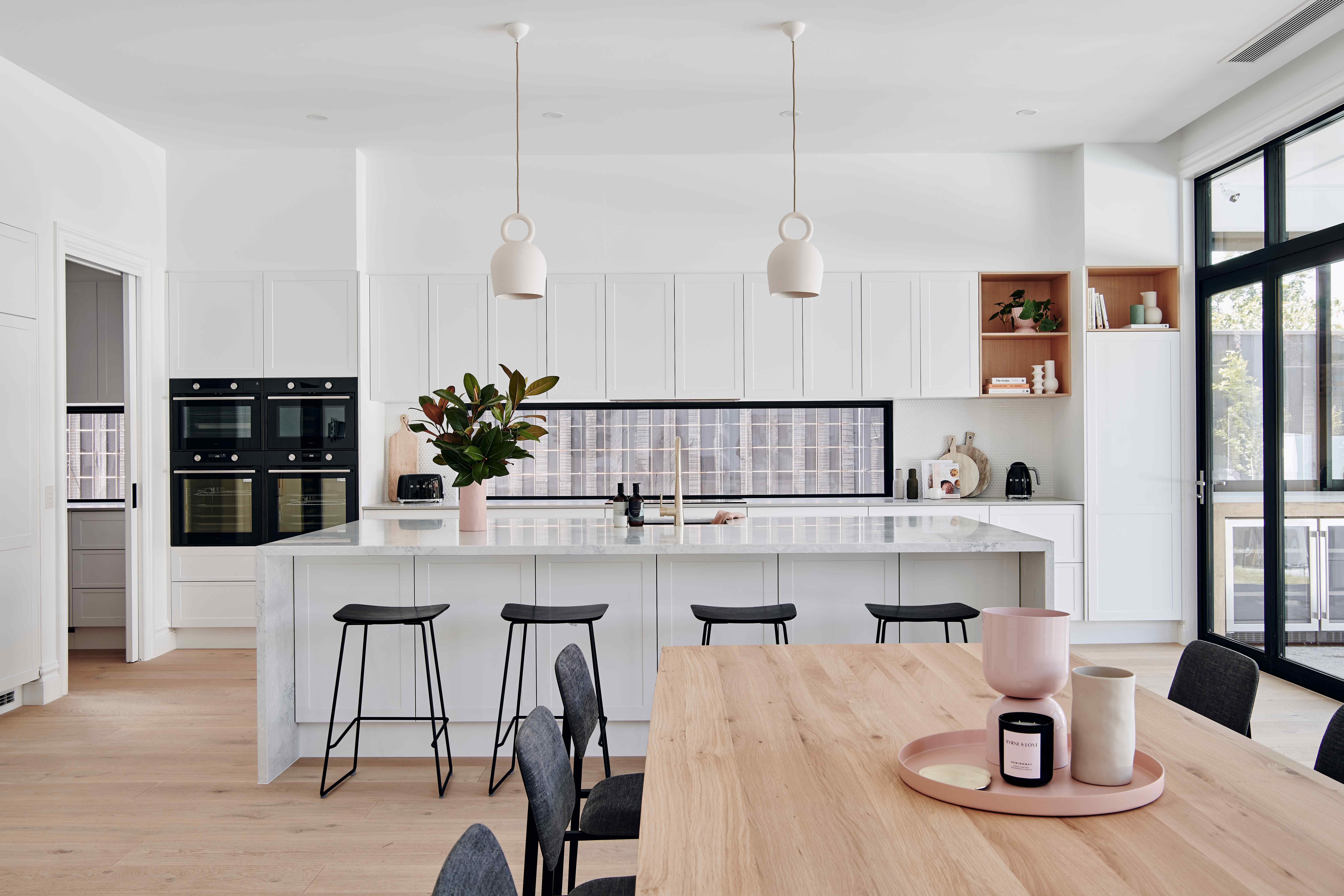 Velká bílá kuchyň s barovými židlemi a jídelní kout